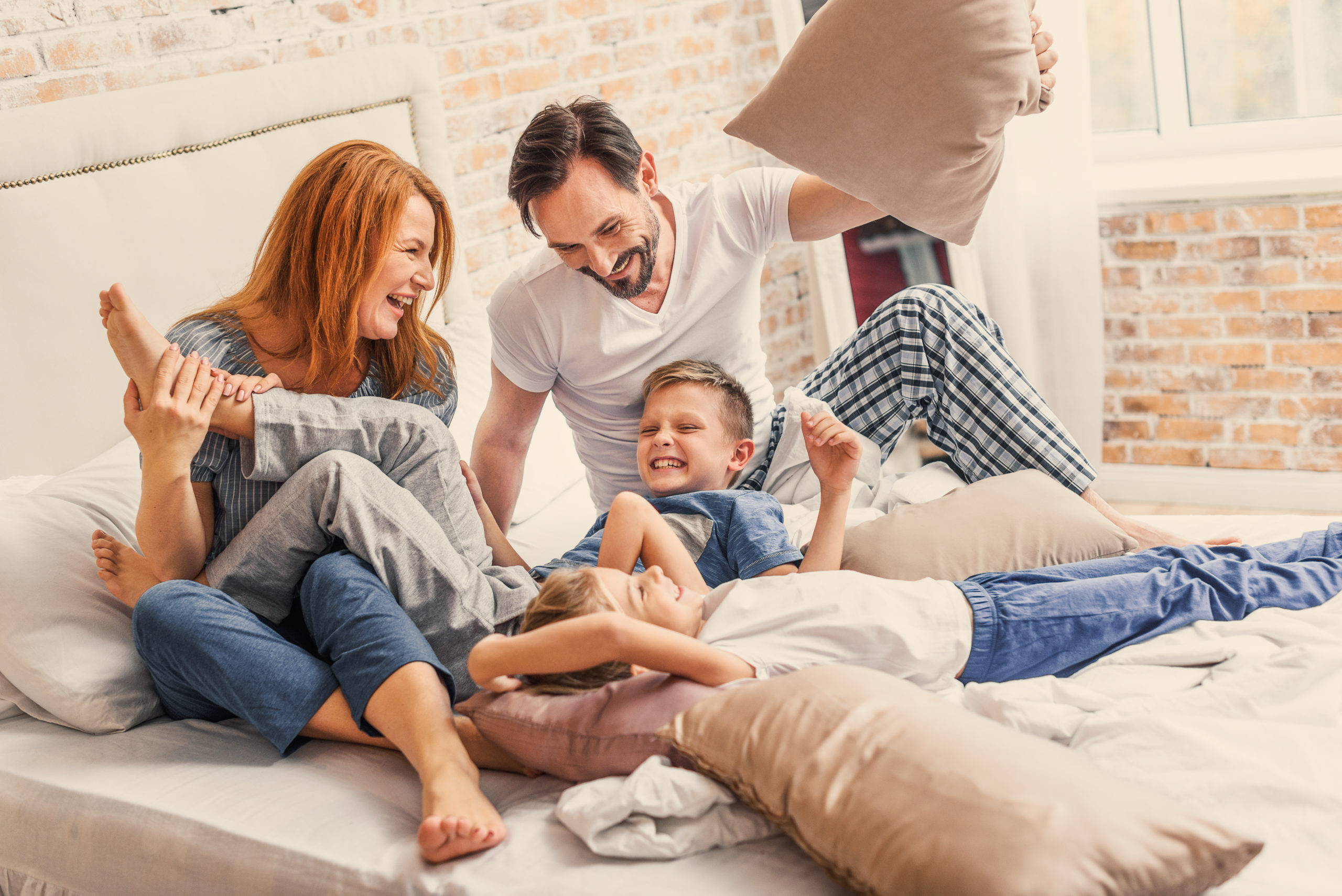 Joyful parents spending time with their smiling children while playing with pillows in bed